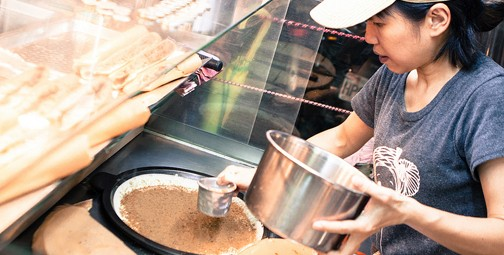 Food being prepared at an open-air food stall. Photo by Jirka Matousak